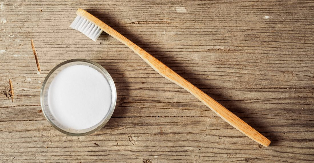Baking soda and toothbrush on a wooden board