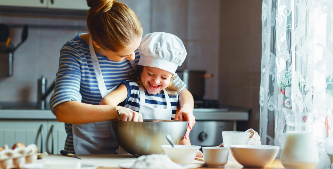Mother and daughter learning to cook in the kitchen