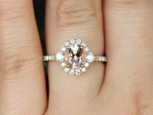 An oval morganite halo engagement ring with conflict-free diamonds and 14kt rose gold band.