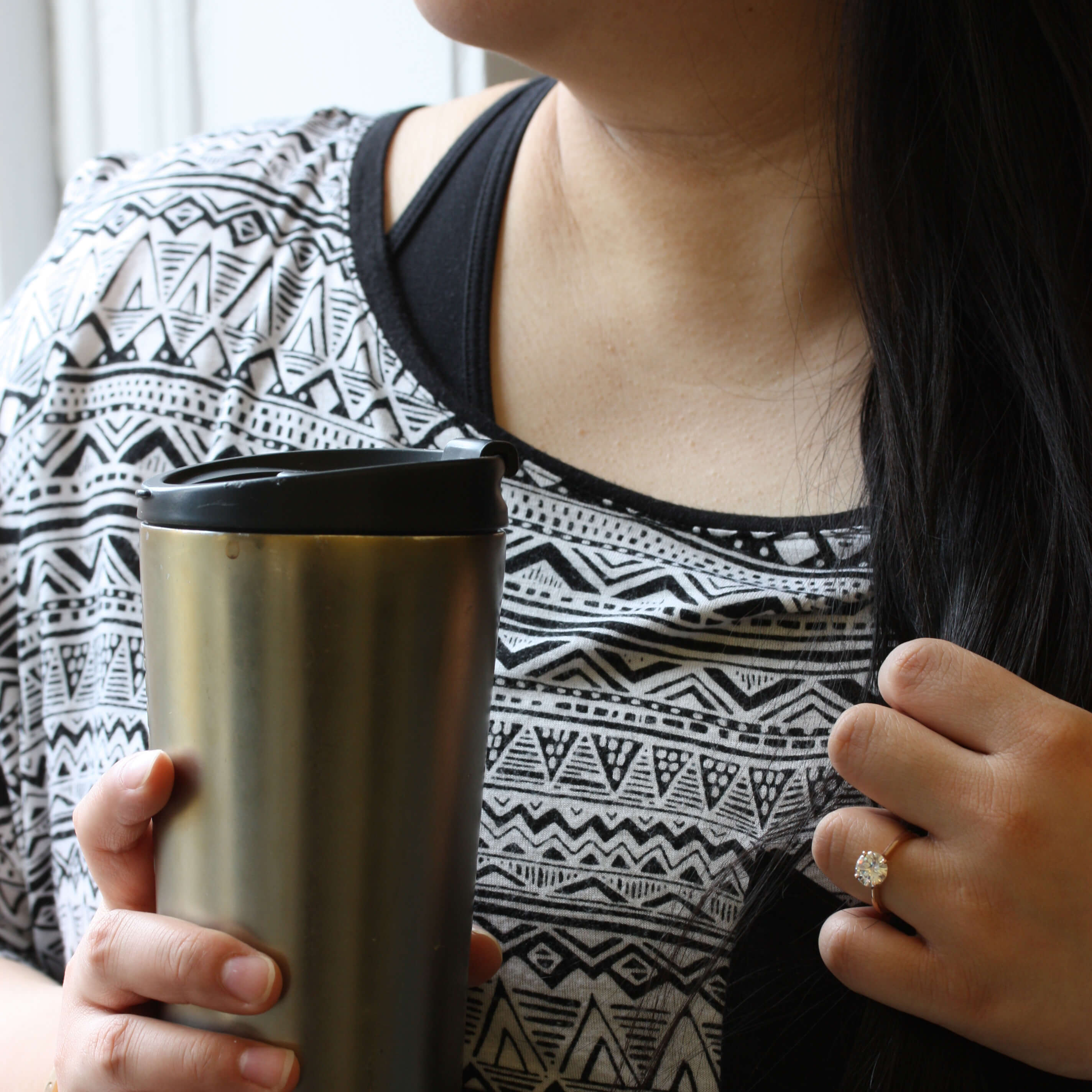 Woman holding a cup of coffee wearing her round gemstone ring