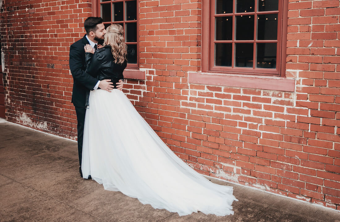 Josh holds Julie on wedding day while kissing her cheek