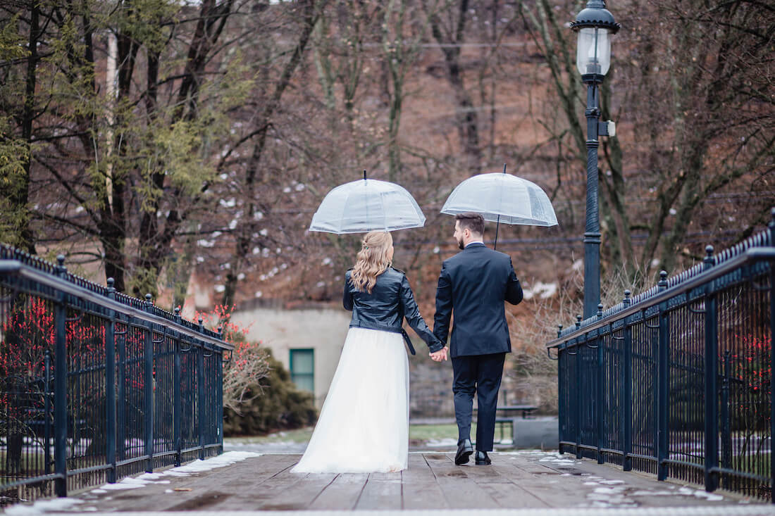 Julie and Josh walking along a bridge holding hands and umbrellas to keep dry