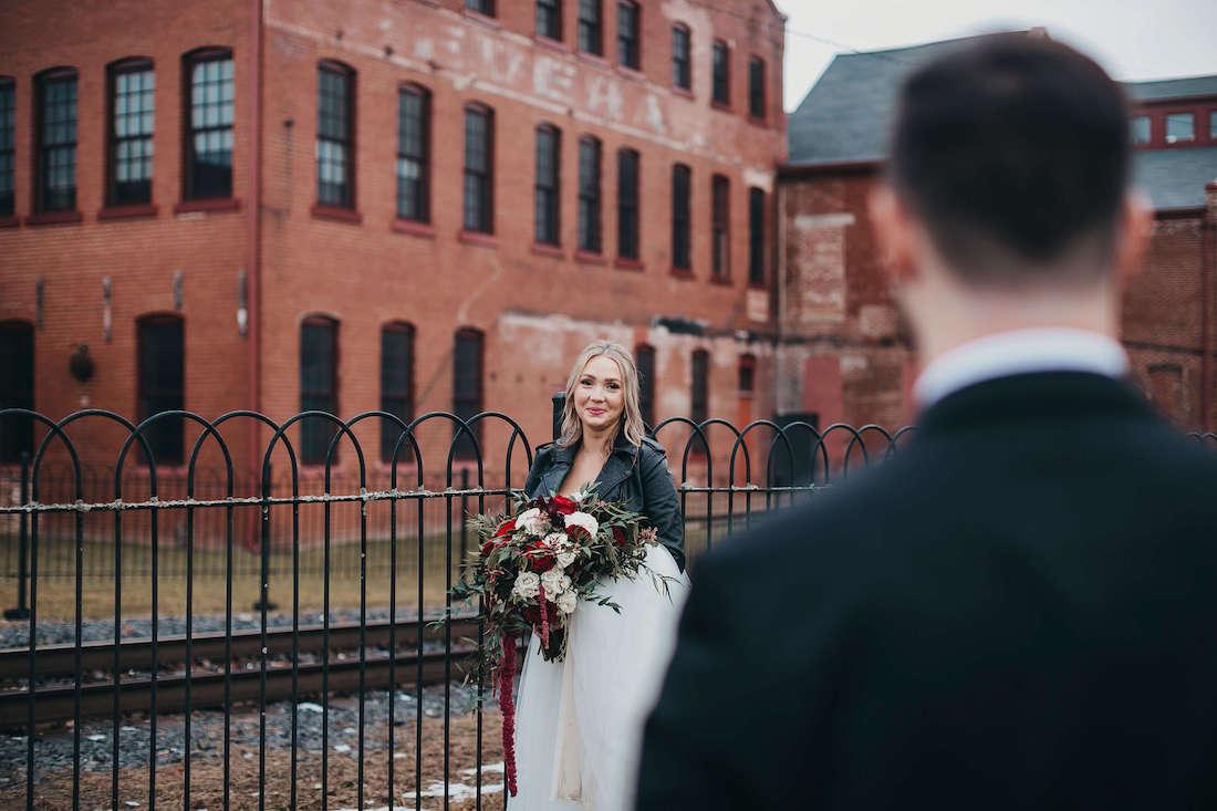 Julie in her wedding dress with a grinning gaze toward a distant Josh