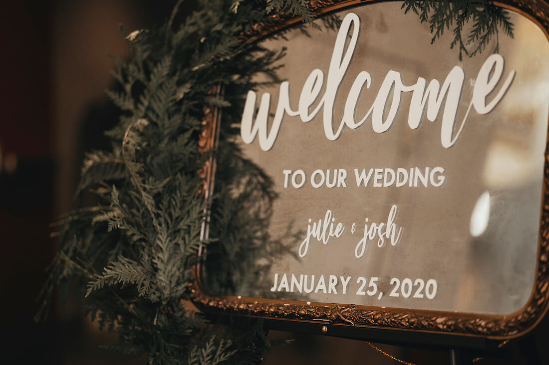 a mirrored sign that reads welcome to our wedding Julie & Josh January 25 2020