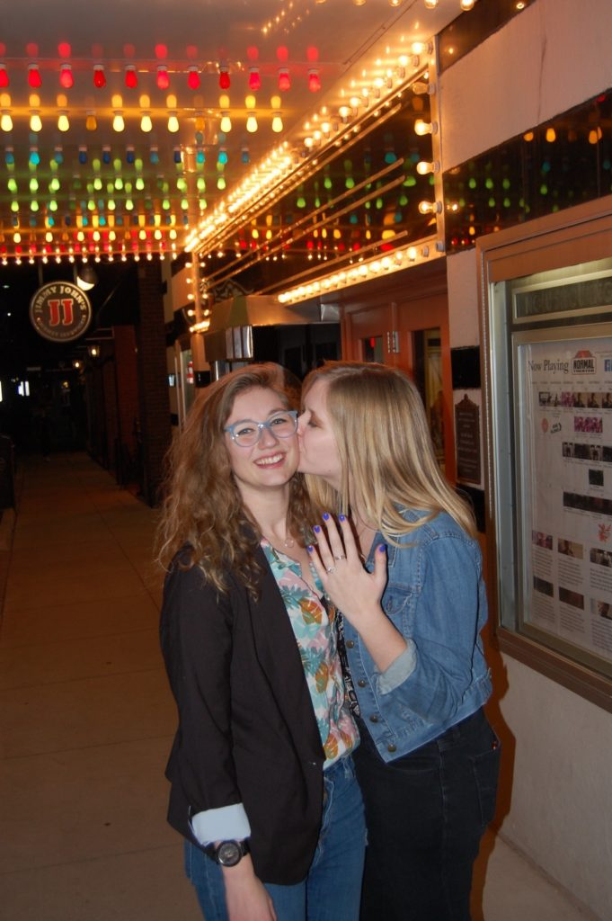 Lexi and Mallory kiss outside the movie theatre after getting engaged.