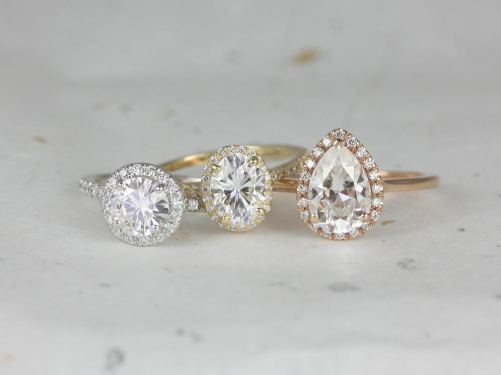 Three differently colored halo engagement rings.