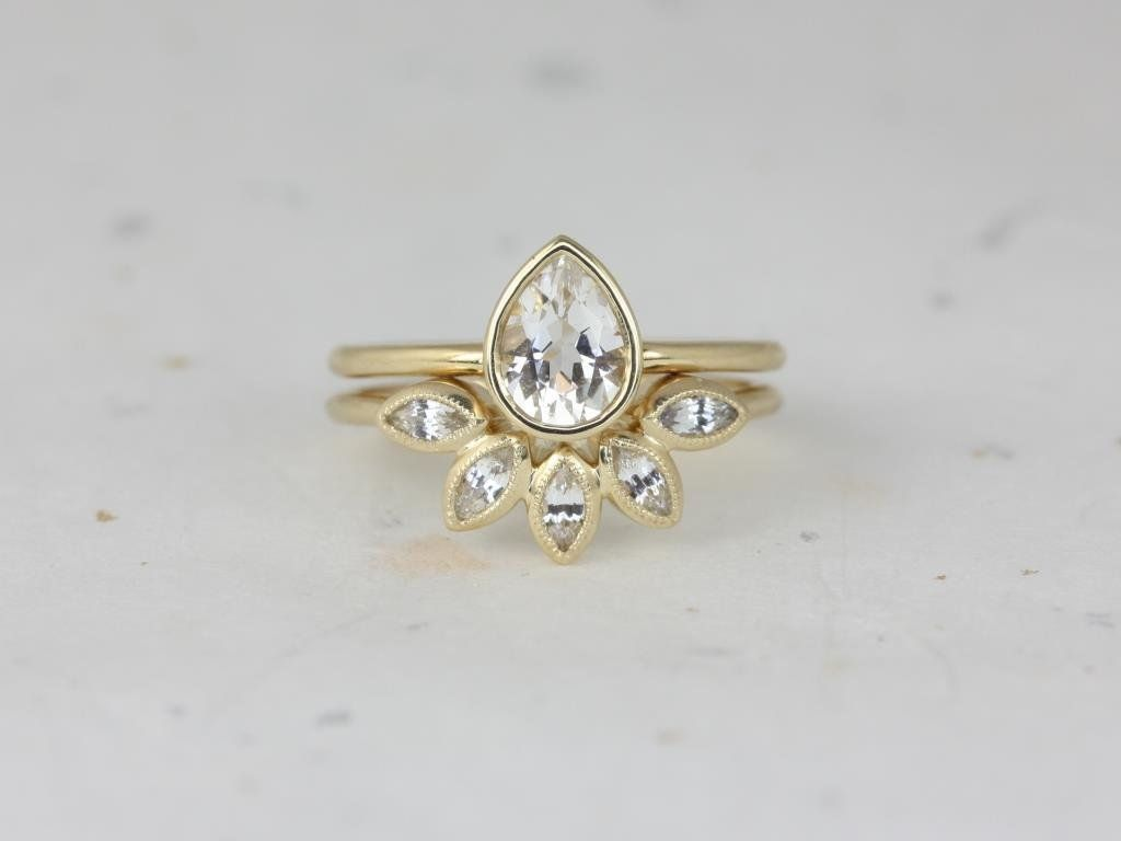 https://www.loveandpromisejewelers.com/media/catalog/product/cache/1b8ff75e92e9e3eb7d814fc024f6d8df/r/o/rosados_box_diamond_free_isla_7x5mm_petunia_14kt_yellow_gold_pear_white_sapphire_bezel_petal_wedding_set.jpg
