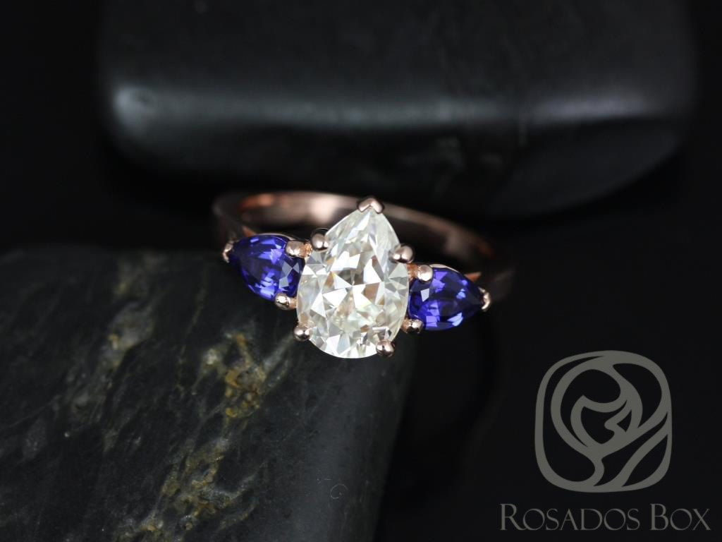 https://www.loveandpromisejewelers.com/media/catalog/product/cache/feefdef027ccf0d59dd1fef51db0610e/k/a/kasey_10x7mm_14k_rose_gold_pear_fb_moissanite_and_blue_sapphire_3_stone_engagement_ring_1.jpg
