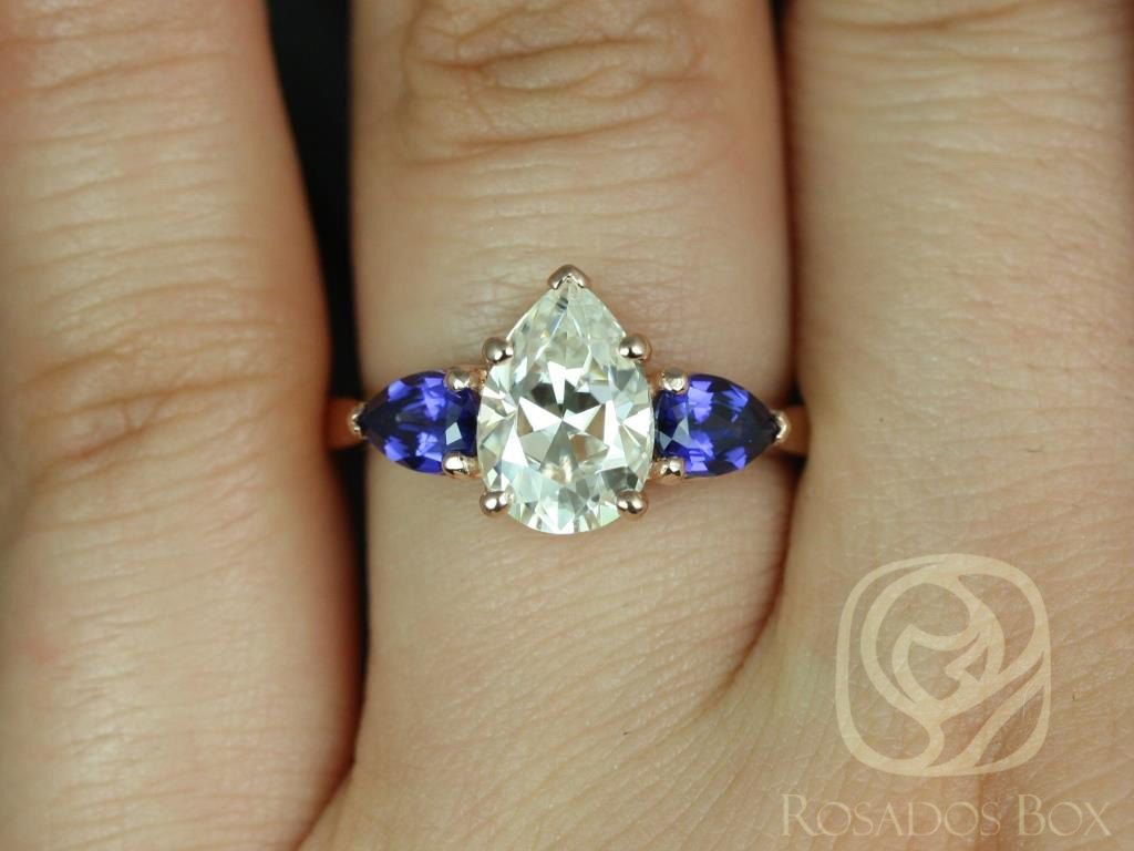 https://www.loveandpromisejewelers.com/media/catalog/product/cache/feefdef027ccf0d59dd1fef51db0610e/k/a/kasey_10x7mm_14k_rose_gold_pear_fb_moissanite_and_blue_sapphire_3_stone_engagement_ring_3.jpg