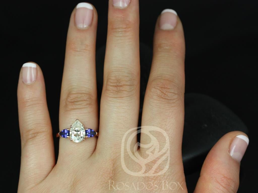 https://www.loveandpromisejewelers.com/media/catalog/product/cache/feefdef027ccf0d59dd1fef51db0610e/k/a/kasey_10x7mm_14k_rose_gold_pear_fb_moissanite_and_blue_sapphire_3_stone_engagement_ring_4.jpg
