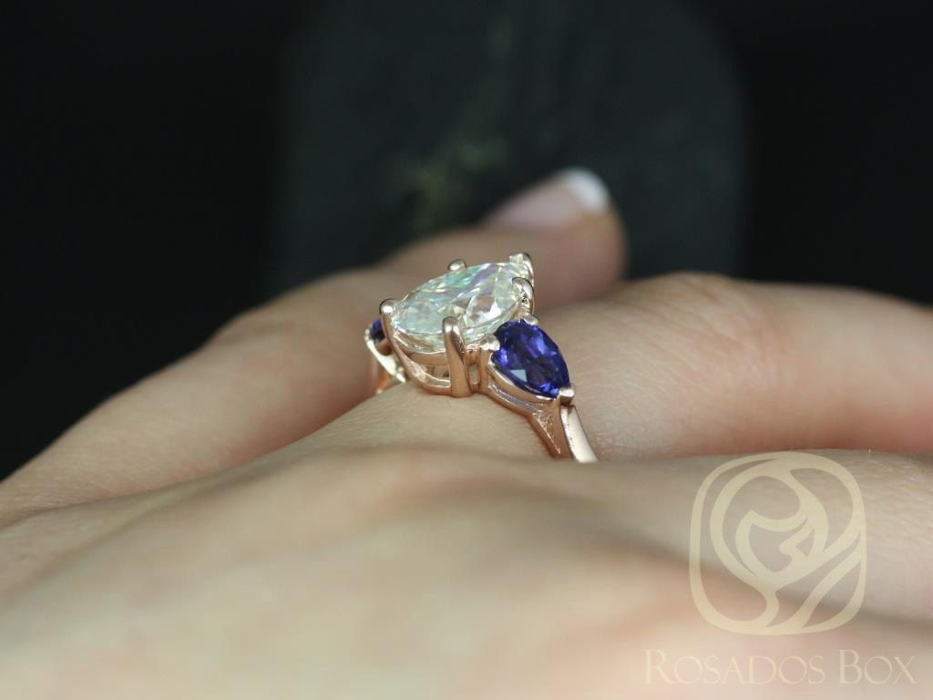 https://www.loveandpromisejewelers.com/media/catalog/product/cache/feefdef027ccf0d59dd1fef51db0610e/k/a/kasey_10x7mm_14k_rose_gold_pear_fb_moissanite_and_blue_sapphire_3_stone_engagement_ring_5.jpg