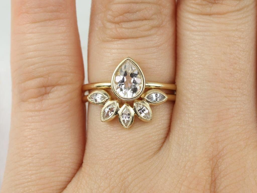 https://www.loveandpromisejewelers.com/media/catalog/product/cache/feefdef027ccf0d59dd1fef51db0610e/r/o/rosados_box_diamond_free_isla_7x5mm_petunia_14kt_yellow_gold_pear_white_sapphire_bezel_petal_wedding_set3.jpg