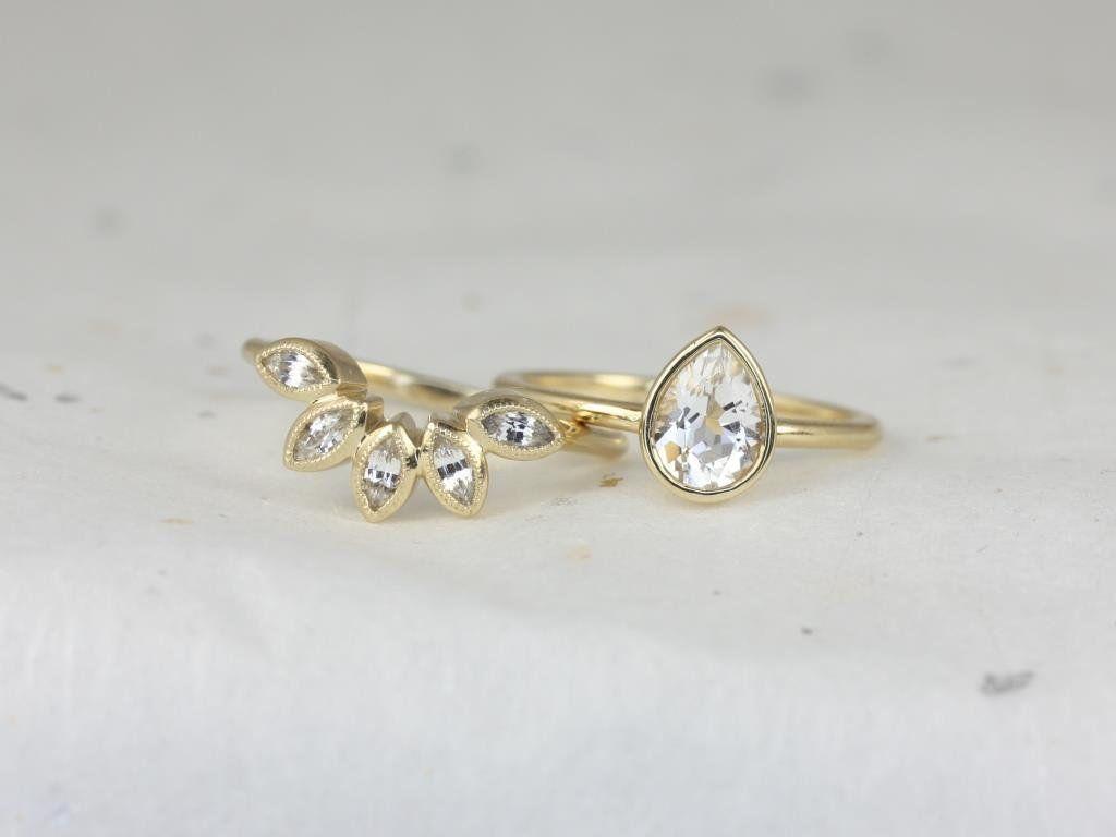 https://www.loveandpromisejewelers.com/media/catalog/product/cache/feefdef027ccf0d59dd1fef51db0610e/r/o/rosados_box_diamond_free_isla_7x5mm_petunia_14kt_yellow_gold_pear_white_sapphire_bezel_petal_wedding_set_2.jpg
