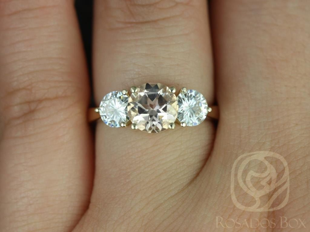 https://www.loveandpromisejewelers.com/media/catalog/product/cache/feefdef027ccf0d59dd1fef51db0610e/t/i/tina_7mm_14kt_yellow_gold_round_morganite_and_fb_moissanite_3_stone_engagement_ring_3wm.jpg