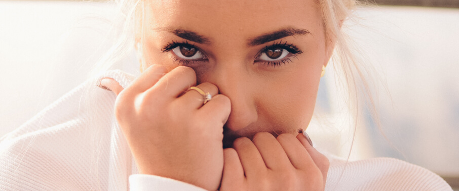 Woman wearing a ring covering her face with her hands | Love & Promise Jewelers