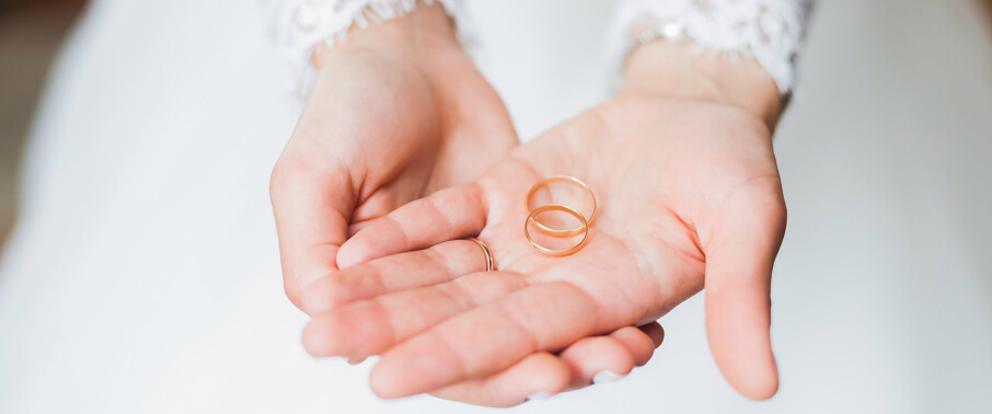 A woman holding out her hands palm up with two wedding bands | Love & Promise Jewelers